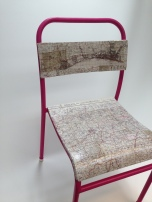 a broken chair is given a new lease of life with an updated paint job and a covering of old maps